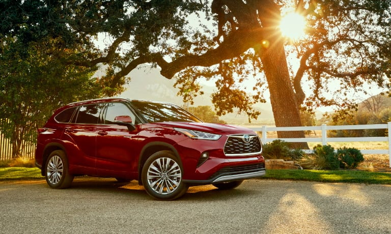 Red 2020 Toyota Highlander parked by a tree during sunset