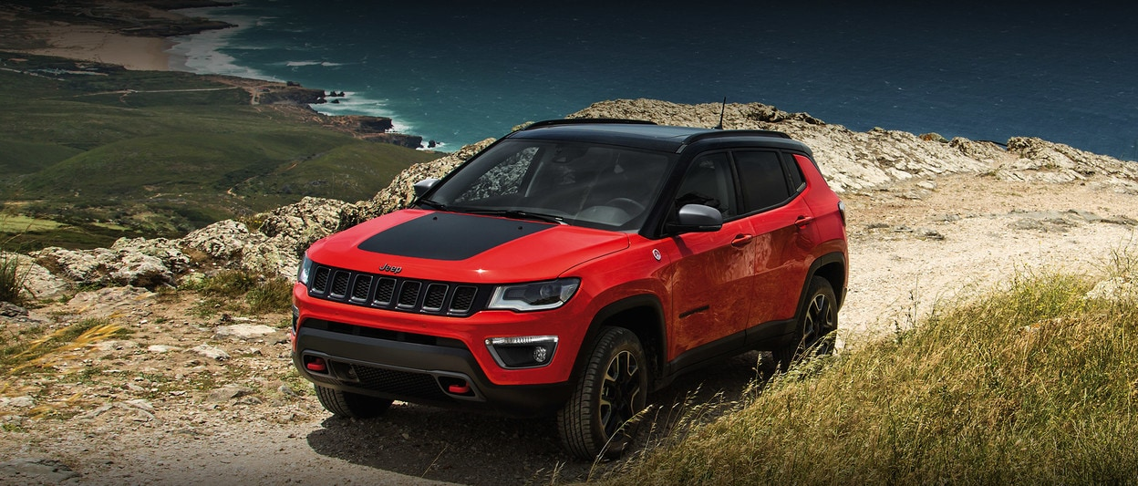 2020 Jeep Compass In Orange Parked In Front of The Ocean