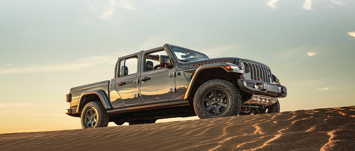 2020 Grey Jeep Gladiator Mojave Parked On Top Of A Sand Hill Desert