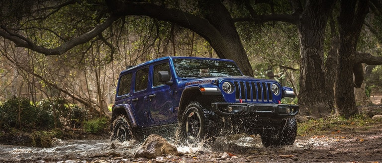 Blue 2020 Jeep Wrangler Driving Through Mud in a forest