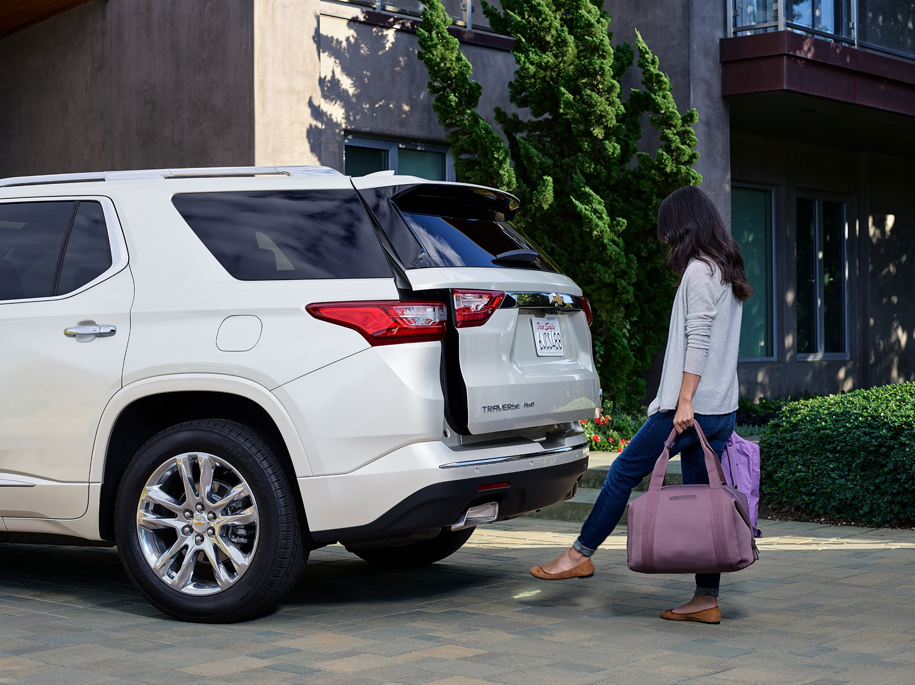 Chevrolet of New Bern is a Car Dealership in New Bern near Bogue NC | Woman accessing trunk of 2020 Chevrolet Traverse