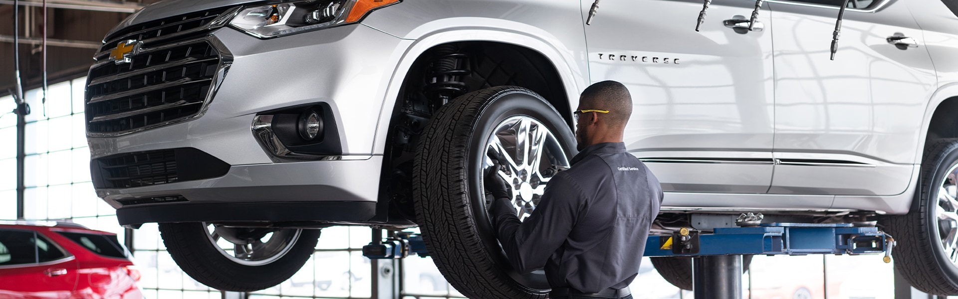 C3 Main Benefits of Using OEM parts for your vehicle at Chevrolet of New Bern | Chevrolet service technician changing tire on silver 2020 Chevrolet Traverse