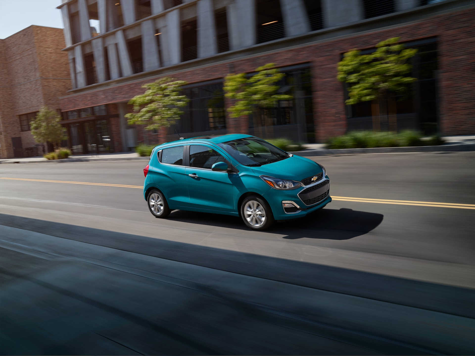 3 Main Benefits of Using OEM parts for your vehicle at Chevrolet of New Bern | Blue 2020 Chevrolet Spark driving downtown