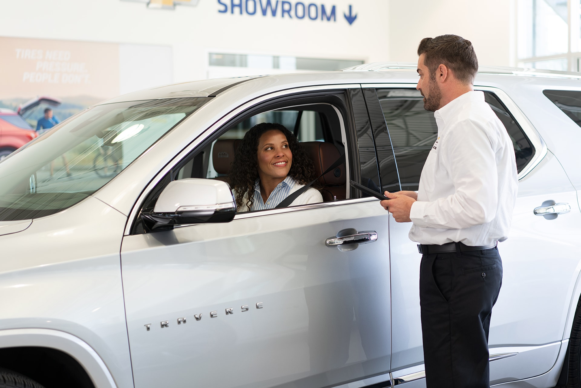 Chevrolet of New Bern is a Car Dealership in New Bern near Bridgeton NC | Chevrolet Service Advisor assisting customer driving White 2020 Chevrolet Traverse in Chevrolet Service Center