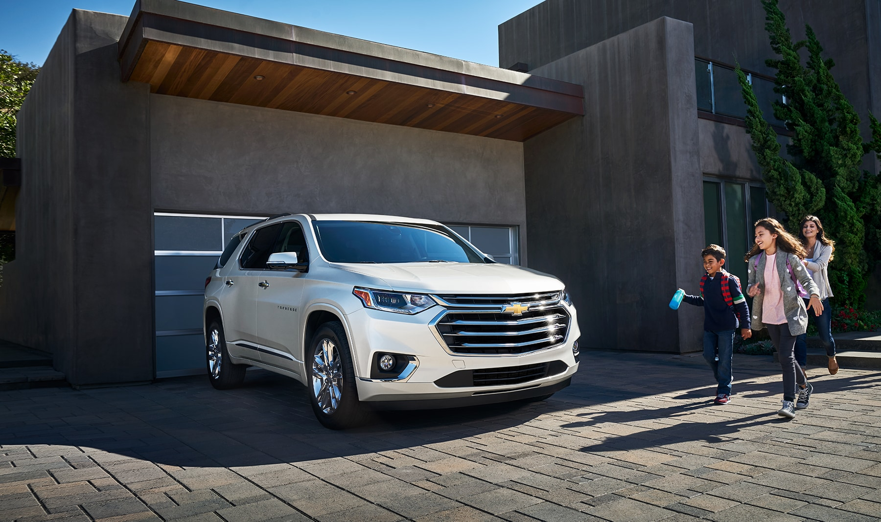 3 Main Benefits of Using OEM parts for your vehicle at Chevrolet of New Bern | Family walking towards 2020 Chevrolet Traverse parked in driveway