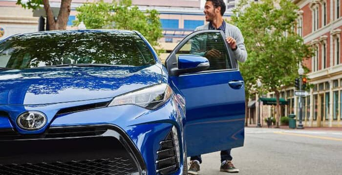 man steps out of 2019 Toyota Corolla