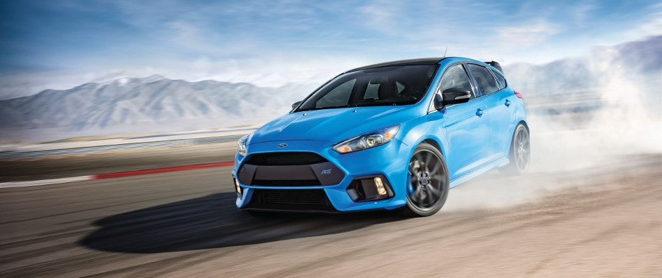 A blue 2018 Ford Focus driving through the dirt
