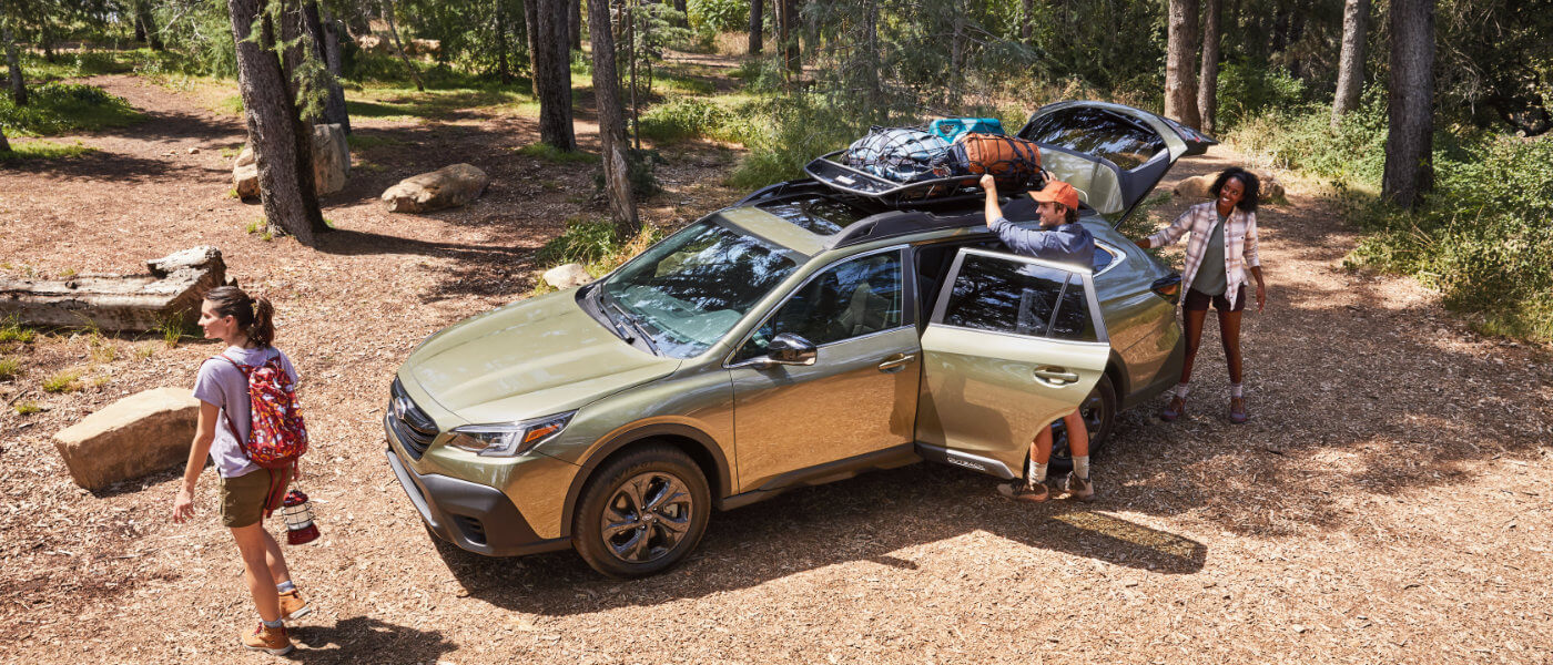 Man Packing up a 2021 Green Subaru Outback in the Forest