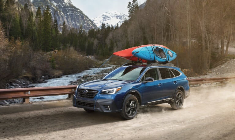 2021 Blue Subaru Outback Hauling Two Canoes on the Roof