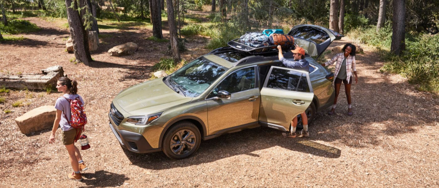 Family Unpacking a 2020 Green Subaru for Camping