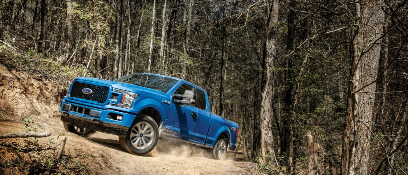 Blue 2020 Ford F-150 driving through the woods