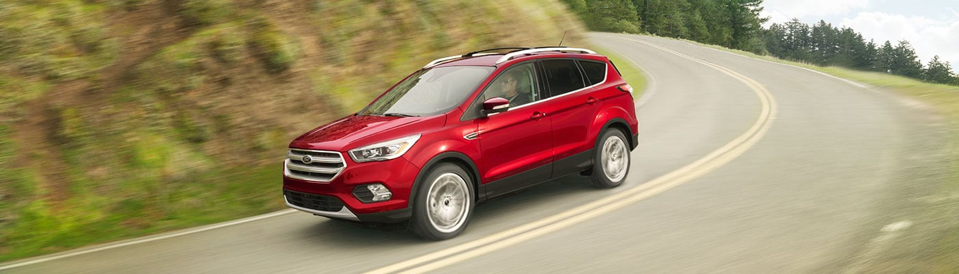 Red 2019 Ford Escape driving down hill