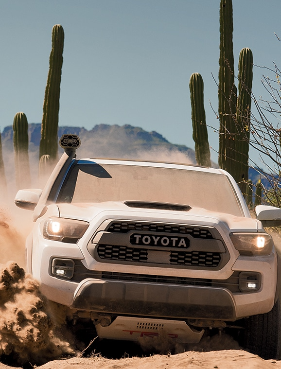 White Tacoma Pro driving through a scenic desert