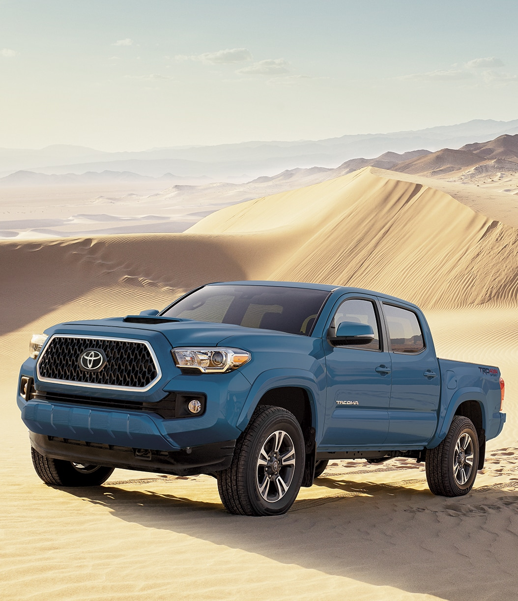 Blue 2019 Tacoma driving through sand dunes