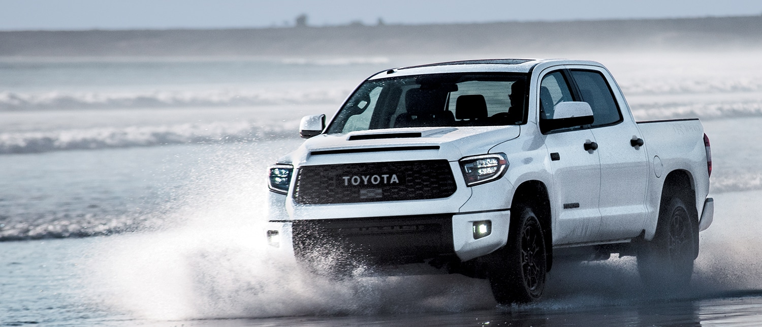 White 2019 Tundra driving through shallow water