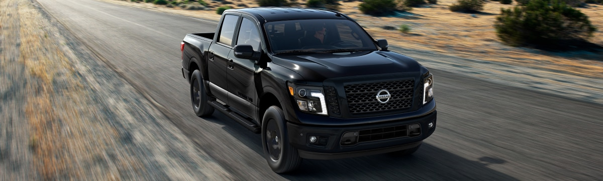 New Nissan Black Titan driving down the road