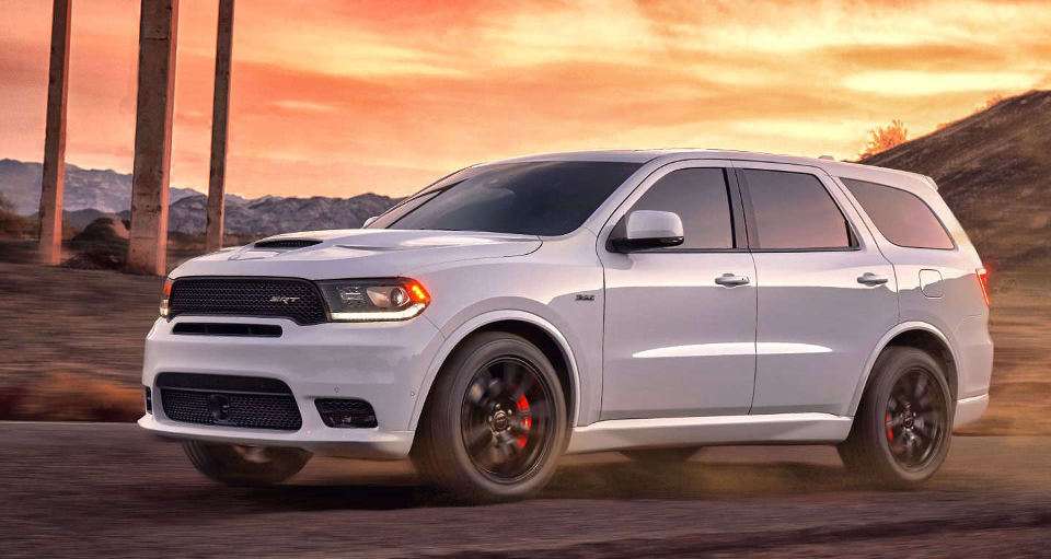 A white 2018 Dodge Durango driving down a road during a sunset
