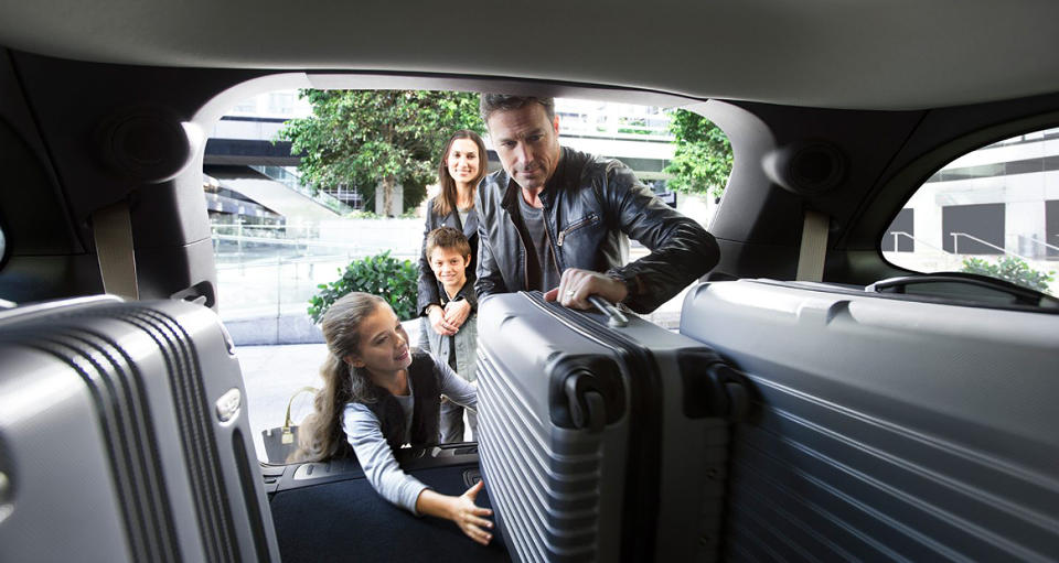 A family loading suitcases into a 2018 Dodge Durango