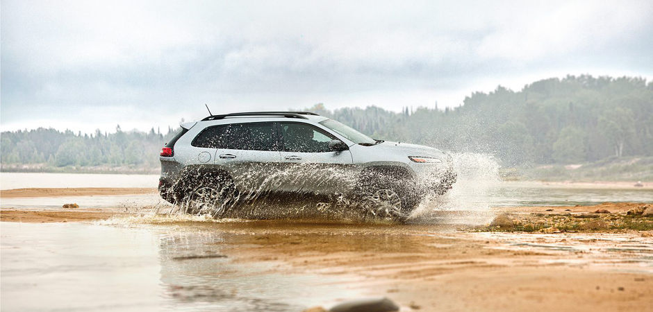 A 2017 Jeep Cherokee driving fast through mud