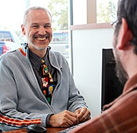 Car salesman smiling at desk