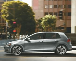 A silver VW hatchback driving through a city