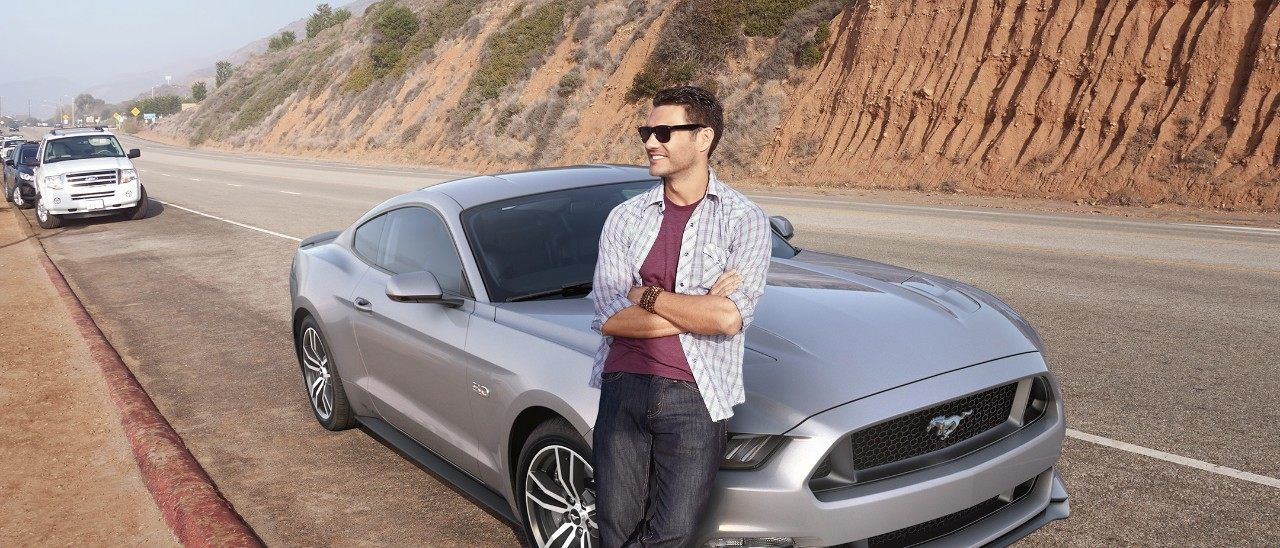 man leans against past model Ford Mustang