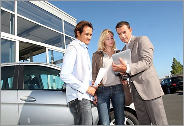 woman and man talking with car sales representative