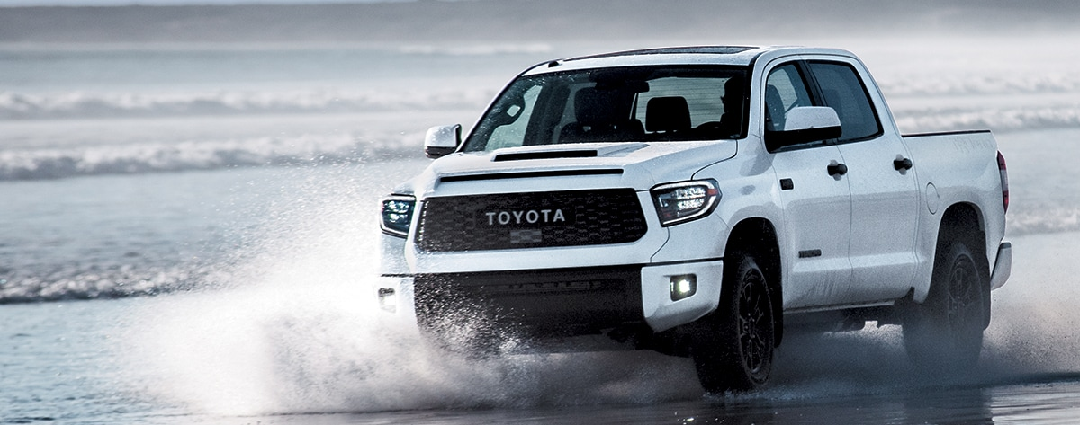 white Tundra driving in the shallow water on a beach