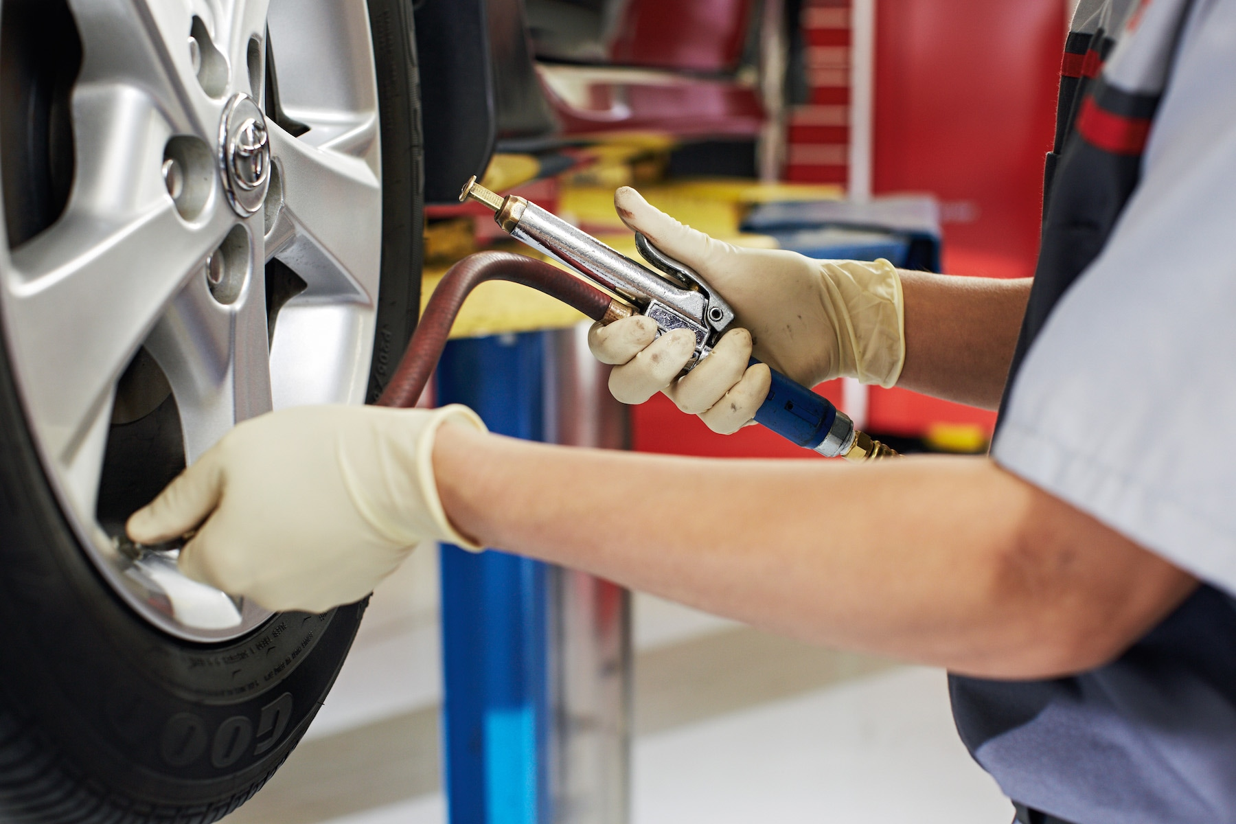How to check your tires' health at Johnstons Toyota of New Hampton | Technician pumping air into tire