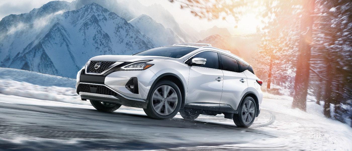 A white 2020 Nissan Murano driving through the snowy mountains