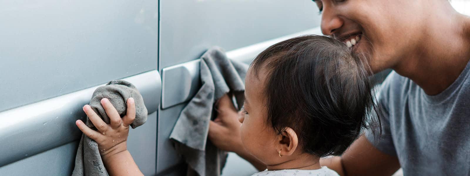 Parent teaching toddler how to wash a car properly