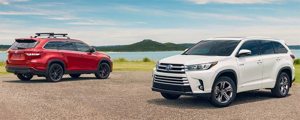 2019 Toyota Highlander showing two models in Blizzard Pearl and Salsa Red Pearl