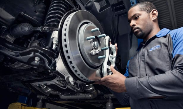 Ford Service technician working on brakes
