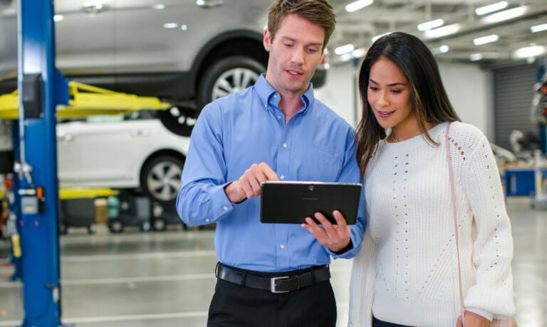 Hyundai service technician on tablet with customer