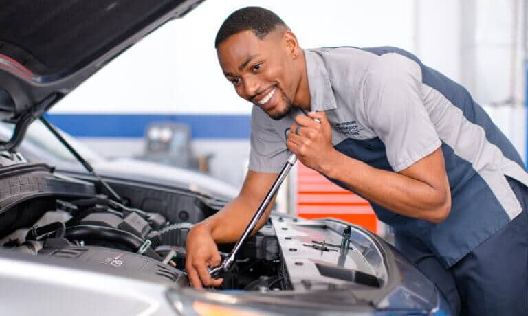 Hyundai service technician looking under hood smiling