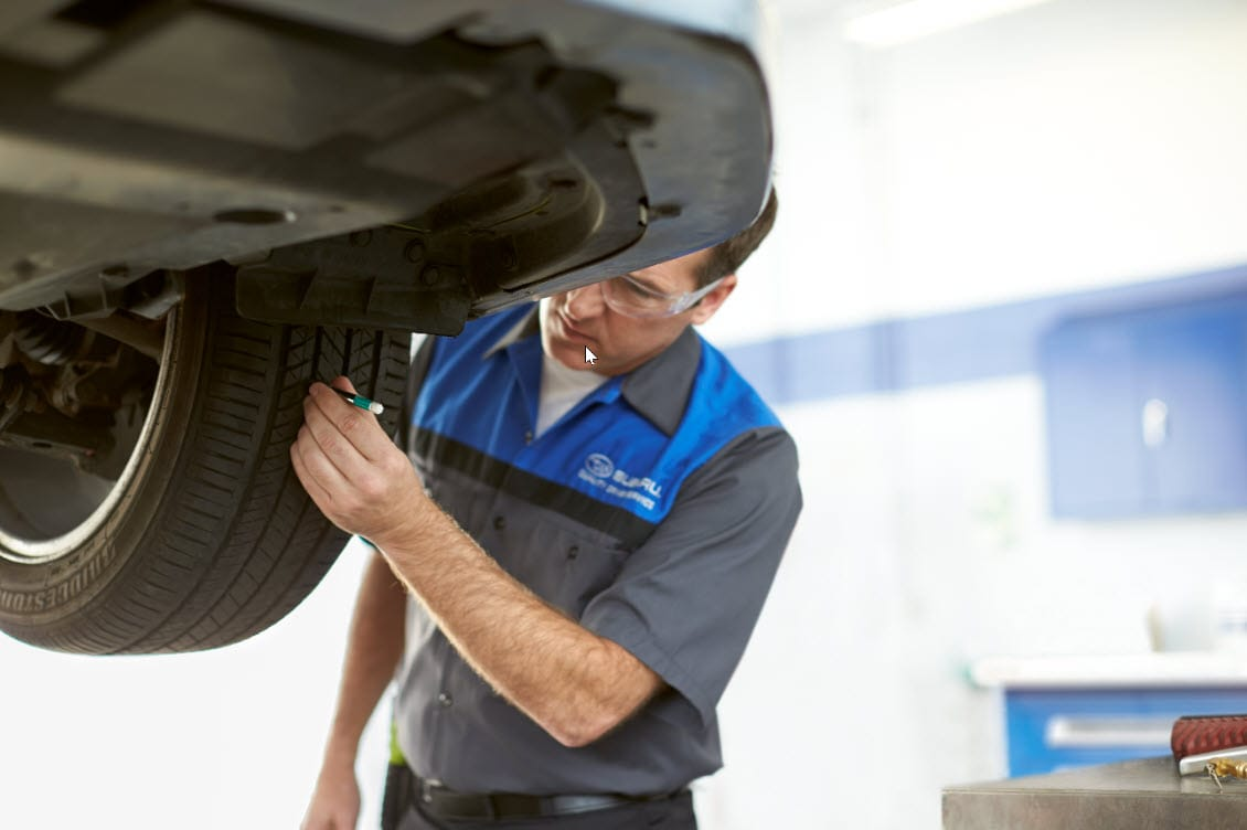 Certified Technician checking tire wear and measuring tire tread depth