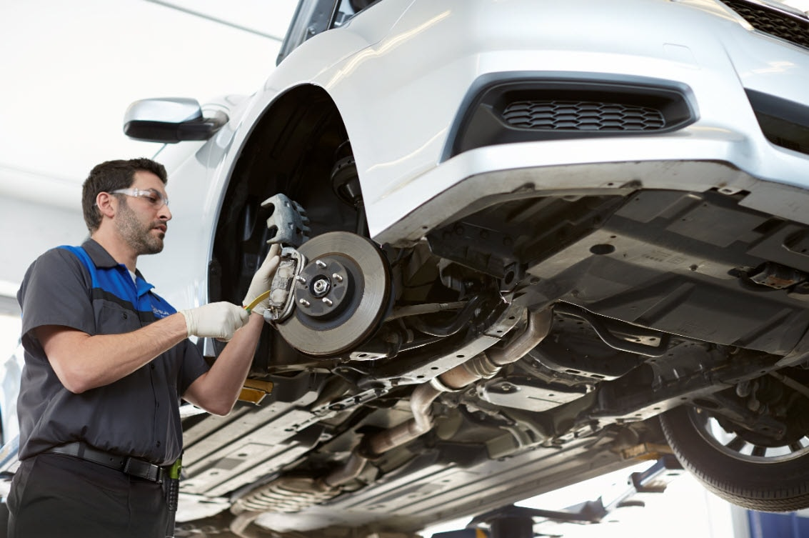 Subaru brake repair technician adjusting brake calipers and checking brake pads