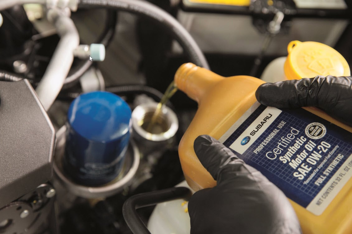 Tech Pouring Genuine Subaru Synthetic Oil During Oil Change