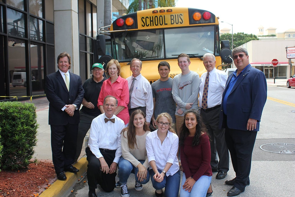 photo of Pinellas County student and staff in front of bus at a local community event