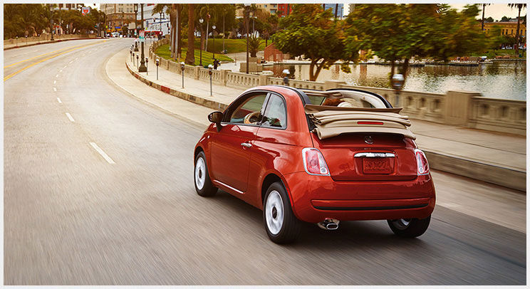 Red 2015 FIAT 500c driving on a winding road with the top down