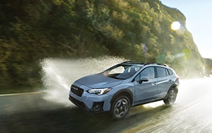 A 2019 Subaru Crosstrek in Cool Grey Khaki utilizes its all-wheel drive on a watery roadway - Northern Arizona's Findlay Subaru Prescott