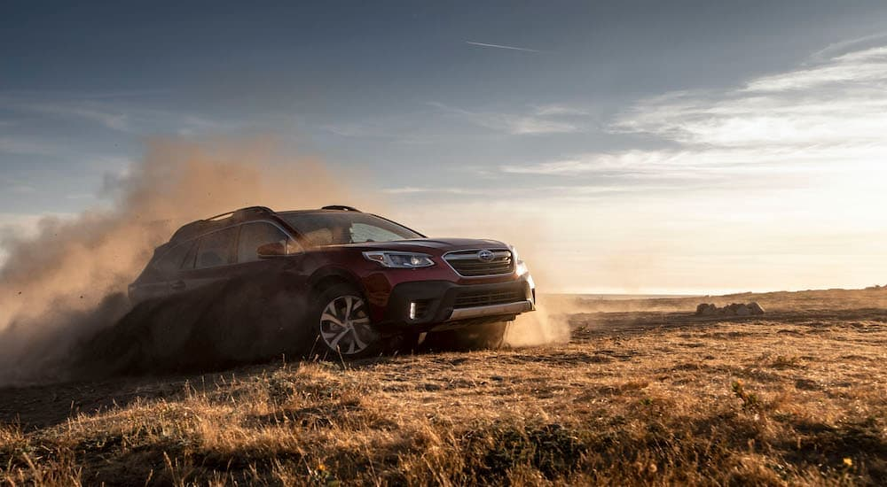A red 2020 Subaru Outback is shown kicking up dust in a dry field after leaving a Charlotte used car dealer.