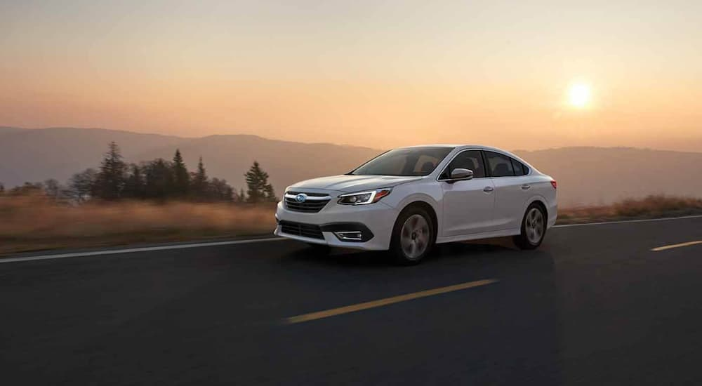 A white 2021 Subaru Legacy is driving past mountains at sunset.