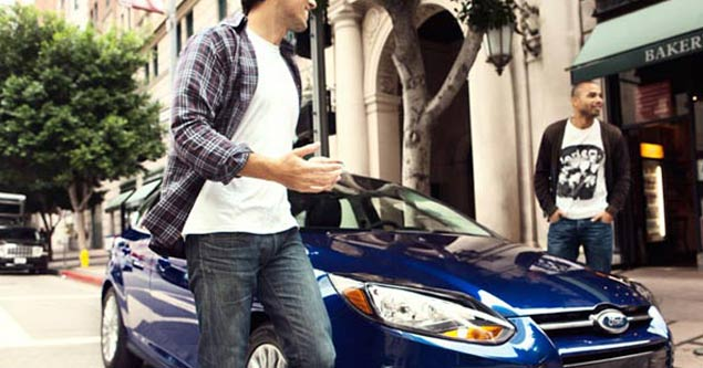 Two gentlemen standing outside their brand new Ford Focus walking onto the sidewalk with smiling faces