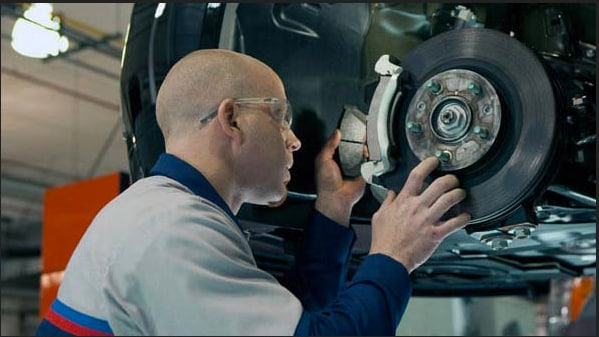 Close up view of a certified Ford technician at Bowen Scarff Ford in Kent near Seattle fixing the brakes on a Ford car
