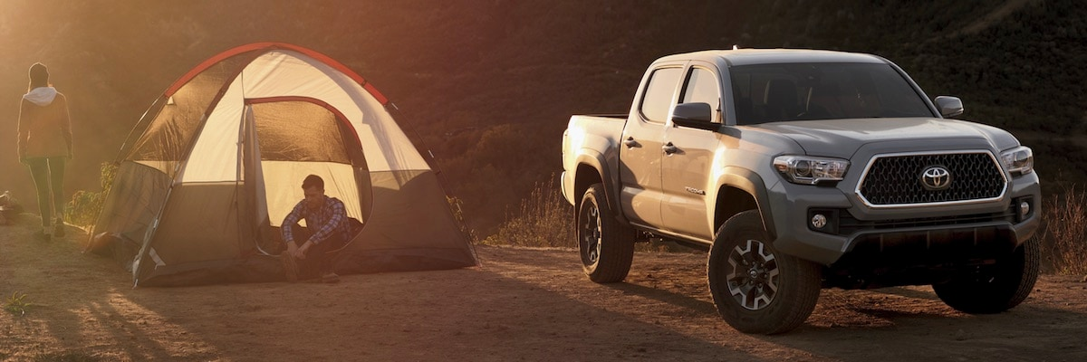 A man and woman going camping with their 2019 Toyota Tacoma