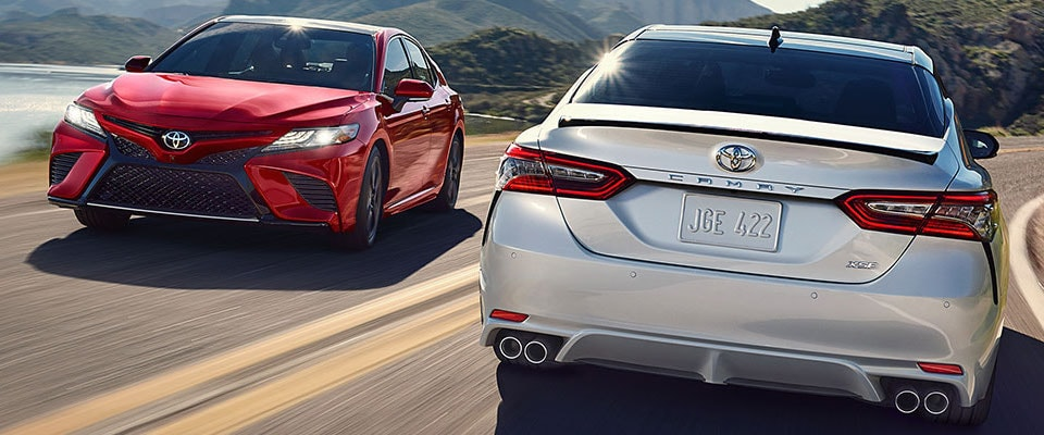 A red & silver 2019 Toyota Camry passing each other on a road