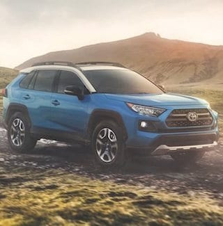 A blue 2019 Toyota RAV4 driving on a dirt path