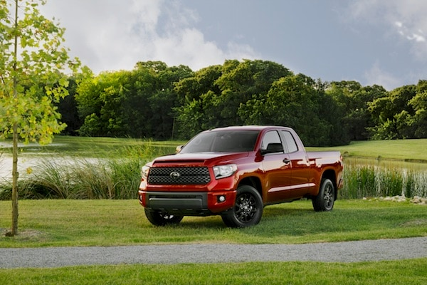 A red 2019 Toyota Tundra parked in a large field by a lake
