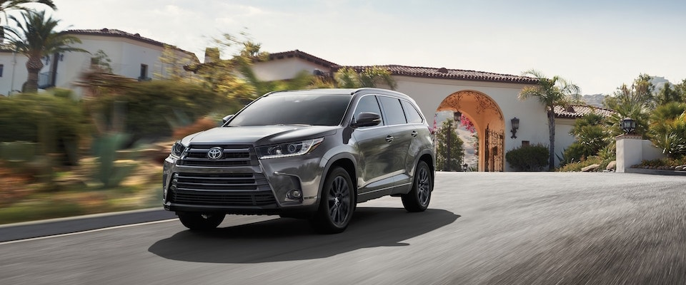 A black 2019 Toyota Highlander driving down the street